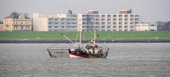 Fischkutter mit Netzen auf der Nordsee vor Cuxhaven. Im Hintergrund eine Wohnanlage mit Ferienwohnungen hinter dem Deich.