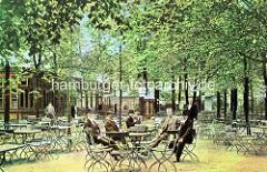 Gartenrestaurant / Café im Wandsbeker Gehölz - Herren mit Hüten, Melonen am Tisch unter Bäumen.