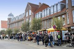 Souvenirshops / Touristen am Wehrbergsweg in Duhnen an der Nordsee - moderne Architektur mit Ferienwohnungen.
