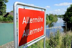 Rotes Stadtteilschild mit weisser Schrift, Allermöhe - plattdeutsch Allermeuh; im Hintergrund der Schleusengraben im Bezirk Hamburg Bergedorf.