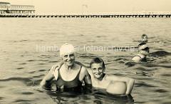 Altes Foto - Badeszene in Duhnen, Menschen im Wasser; im Hintergrund die hölzerne Badebrücke.