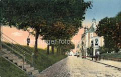 Historisches Motiv, coloriert - Straße mit Kopfsteinpflaster hinter dem Deich in Cuxhaven; Steintreppe mit Eisengeländer zur Deichkrone.