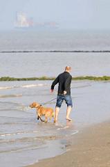 Spaziergänger mit Hund am Elbufer in Otterndorf, der will ins Wasser - Herrchen nicht; im Hintergrund fährt ein Containerschiff elbaufwärts.
