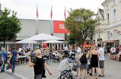 Aussengastronomie / Cafe auf dem Bergedorfer Markt - Tische mit Sonnenschirmen im Freien. Im Hintergrund die Kaufhausarchitektur von Karstadt.