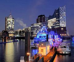 Blick über den Jonashafen / Sportboothafen zum Bürogebäude am Kehrwieder und der  Elbphilharmonie in der Hamburger Hafencity - im Vordergrund blau beleuchtete Fahrgastschiffe der Hamburger Hafenrundfahrt.