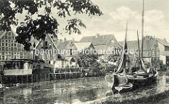 Altes Bild von Otterndorf und dem Fluß Medem - Fachwerkhäsuer mit kleinem Garten oder Scheune am Flussufer; Wäsche ist zum Trocknen aufgehängt - ein Ewer mit Beiboot liegt vor Anker.