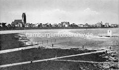 Hochwasser am Deich von Cuxhaven - altes Foto der Stadt, Blick auf die Häuser hinter dem Deich und den Kirchturm der Marine-Garnisionskirche.