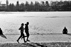 Winteraufnahme aus Hamburg - Jogger am großen See im Hamburger Stadtpark, andere sitzen am Ufer des eisbedeckten Sees in der Sonne.