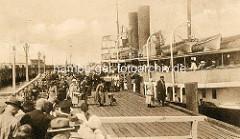 Bilder aus dem alten Cuxhaven - ein Ausflugsschiff legt an der Alten Liebe an - Passagiere steigen aus, andere warten auf dem Holzsteg.