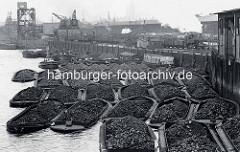 Gleisanlagen der Hafenbahn am Kirchenpauerkai im Hamburger Hafen. Waggons mit Kohle werden auf Schuten entladen.