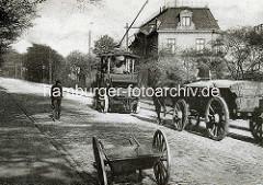 Historische Aufnahme vom Elbberg in Hamburg Altona - ein Zugwagen der elektrifizierten Hafenschleppbahn zieht / unterstützt ein Pferdefuhrwerk bei seiner Fahrt bergauf; ein Fahrradfahrer sieht zu - im Vordergrund eine Handkarre der Strassenreinig
