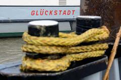 Poller mit Tau - Klampe belegt am Fähranleger, Schriftzug Glückstadt.