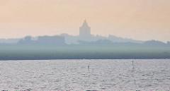 Morgennebel über der Insel Neuwerk - Kühe auf der Weide; im Hintergrund der Nordseedeich / Leuchtturm.