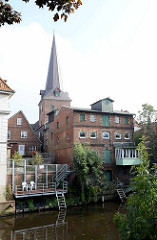 Wohnhäuser und Speicher am Ufer der Medem in Otterndorf - Kirchturm der St. Severi Kirche.