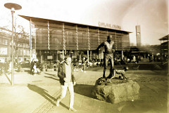 """Marktplatz von Hamburg Wandsbek - Café und Skulptur Der Freudensprung. Die Skulptur stellt den Hamburger Dichter und """"Wandsbeker Boten"""" Matthias Claudius beim Sprung über einen seiner Söhne; ein altes Ritual aus dem 18. Jahrhundert, das bei der Geb"""