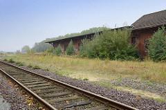 Bahngleise - mit Sträuchern zugewachsene Bahngebäude vom Güterbahnhof in Cuxhaven.