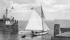 Ein Sportboot Segelschiff mit Ruderboot im Schlepp läuft aus dem Hafen von Cuxhaven aus - es passiert die Hafenmole der Alte Liebe.