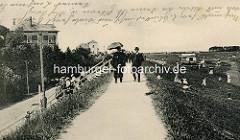 Altes Bild aus Cuxhaven - Urlaubsgäste mit Sonnenschirm auf dem Weg der Deichkrone - Restaurant & Garten Etablissement.