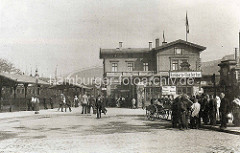 Empfangsgebäude vom Bahnhof Hamburg Klostertor; Passagiere mit Koffer / Handkarren. Im Hintergrund das Gebäude vom 1906 in Betrieb genommenen Hauptbahnhof.