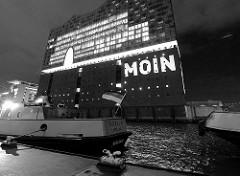 Tag der Eröffnung der Elbphilharmonie in der Hamburger Hafencity - 11. Januar 2017;  Schriftzug Moin an die Fassade gestrahlt - im Vordergrund Schiffe am Anleger Sandtor / Deutschlandfahne.