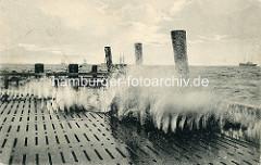 Wellengang der Elbe an der Alten Liebe in Cuxhaven - die Gischt spritzt durch die Rillen vom Landungssteg.