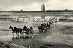 Historisches Foto von Wattwagen im Wasser - Personenwagen mit Touristen von Pferden gezogen auf den Weg von der Insel Neuwerk nach Duhnen / Cuxhaven. Im Hintergrund der Leuchtturm und Wohnhäuser hinter dem Deich.