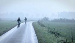Radausflug im Herbst - Radfahrer / Radfahrerin auf einem Feldweg im Nebel bei Otterndorf  am Liebesweg / Zutrifft.