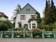 Villa mit Holz- und Ziegelfassade - farbig abgesetzter Gartenzaun mit Steinpfeilern und Gitter, blühende Hortensien; Hamburg-Amerika-Straße in Cuxhaven.
