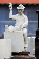 Steinmetz bei der Arbeit - Skulptur eines Steinmetzbetriebes in Cuxhaven.