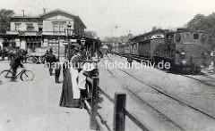 Altes Bild vom Klostertorbahnhof in Hamburg - Lokomotive mit Personenwaggons - Mutter mit Kind am Zaun, Fahrradfahrer  und Pferdefuhrwerk.