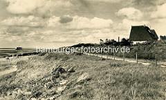 Alte Fotografie von der Nordseeküste bei Duhnen - Ferienhaus mit Reet gedeckt, im Hintergrund die Badebrücke.