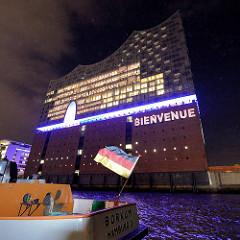 Tag der Eröffnung der Elbphilharmonie in der Hamburger Hafencity - 11. Januar 2017;  Schriftzug Bienvenue wird an die Fassade gestrahlt - im Vordergrund Schiffsheck am Anleger Sandtor / Deutschlandfahne.