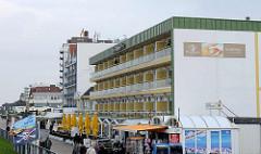 Moderne Bäderarchitektur hinterm Deich von Duhnen / Cuxhaven; mehrstöckige Gebäude / Wohnanlagen / Apartmenthäuser mit Ferienwohnungen - Restaurant mit Aussengastronomie.