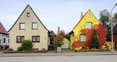 Einzelhäuser / Wohnhaus mit Satteldach - unterschiedliche Fassadengestaltung; gelbe Ziegel, gelb gestrichener Fassade - Kletterpflanze, Weinlaub in Herbstfarben.
