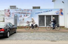 Leerstehendes Ladengeschäft, Fabrik Verkauf - Fassadenmalerei Fischkutter, Männer mit Fisch; FahrradfahrerIn in der Neufelder Straße von Cuxhaven.