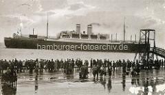 Ein Passagierschiff liegt auf Reede vor Cuxhafen - Schaulustige stehen am Steg der Alten Liebe.
