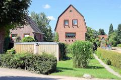 Einzelhäuser mit Vorgarten - schmales Ziegelgebäude / Wohnhaus mit Mansardach.