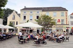 Aussengastronomie / Cafe auf dem Bergedorfer Markt - Tische mit Sonnenschirmen im Freien.