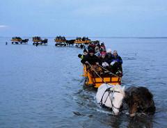 Wattwagen mit Touristen in hohem Nordseewasser auf dem Weg von Neuwerk nach Duhnen / Cuxhaven.