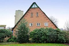 Nordfront vom Bauernhaus in Tangstedt / Ortsteil Wilstedt;  Holzgiebel mit grün / weisser Verkleidung - Eisenfenster vom Heuboden, Holzfenster vom Wohnbereich - im Hintergrund ein Silo.