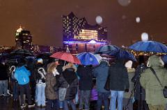 Tag der Eröffnung der Elbphilharmonie in der Hamburger Hafencity - 11. Januar 2017; Schaulustige / Fotografen mit Regenschirmen bei regnerischem Wetter blicken über die Elbe zur beleuchteten Elbphilharmonie.
