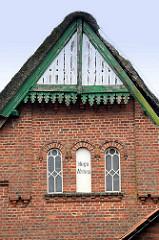 Holzgiebel mit Zierverleistung - grün / weiss; Ziegelmauer - Eisenfenster / Fensterrahmen - Schriftzug Hugo Ahlers. Bauernhaus in Tangstedt / Ortsteil Wilstedt.
