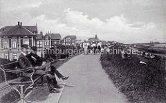 Alte Fotografie vom Deich in Cuxhaven - zwei Männer mit Mütze sitzen auf einer Ruhebank, eine Personengruppe geht auf dem Deich spazieren.