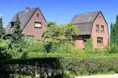 Einzelhäuser mit Vorgarten - schmales Ziegelgebäude / Wohnhäuser mit Satteldach + Mansardach.