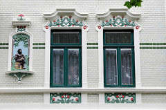 Jugendstil / Art Nouveau - Hausfassade, Wohnhaus in Cuxhaven; Fensterumrandung mit farbigem floraren Stuck - weisse Ziegelfassade mit grünem Band.