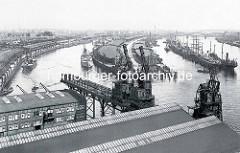 Historische Hafenansicht von Hamburg - Blick auf den Baakenhafen, lks. der Versmannkai und die Bögen der Pfeilerbahnstrecke - re.  Lagerschuppen und  Frachtschiffe am Petersenkai. Im Flusslauf der Norderelbe liegen Frachtsegler und Frachter an den