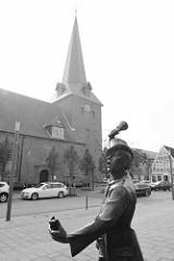 Skulptur der Utröper / Ausrufer, Bildhauer Frijo Müller-Belecke am Kirchplatz in Otterndorf - im Hintergrund die St. Severi Kirche.