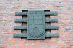 Backsteinarchitektur am Bahnhof von Cuxhaven - Hamburg Wappen mit Fischen.