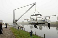 Am Hadelner Kanal wird in Otterndorf ein Segelschiff gekrant, mit einem Kran für das Winterlager an Land gehievt.