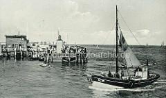 Ein Fischkutter läuft in den Hafen von Cuxhaven ein - Paddelboot auf dem Wasser; Holzsteg mit Schaulustigen an der Alten Liebe - Signalfeuer der Hafeneinfahrt.